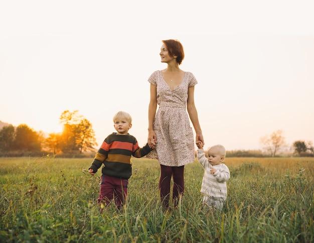 야외 자연에서 일몰에 햇빛에 아이들과 함께 젊은 어머니