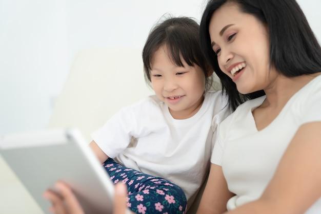 自宅で一緒にデジタルタブレットを使用して子供を持つ若い母親。画面を見たり、おもちゃを買い物したり、オンラインで漫画を見たりする家族の笑顔、