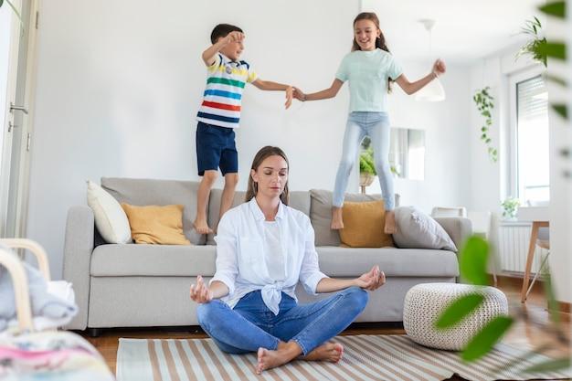 目を閉じて蓮華座で瞑想している若い母親は、ソファに飛び乗って明るく広々としたリビングルーで叫んでいる興奮した子供たちが内側の調和を救おうとしています。