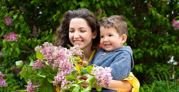 곱슬 머리와 꽃을 들고 아이 젊은 어머니.