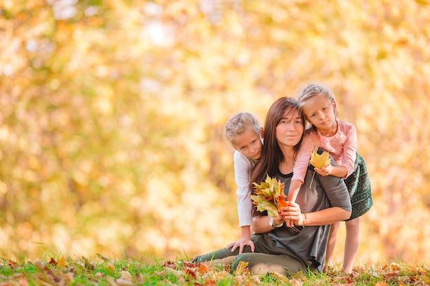 晴れた日に秋の公園でかわいい女の子を持つ若い母親。家族は9月の日に暖かい天候を楽しむ