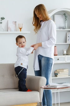 A young mother with a cute little son is having fun in a bright cozy living room