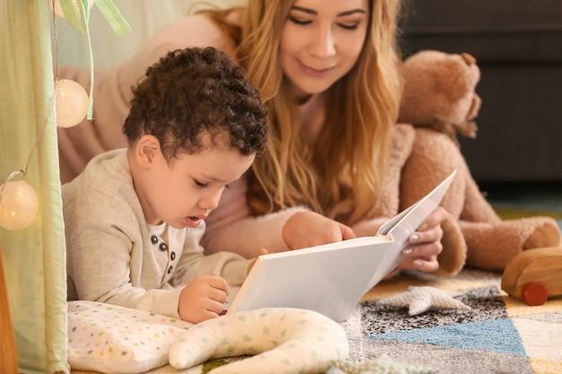 집에서 오두막집에서 귀여운 작은 아들 읽기 책 젊은 어머니