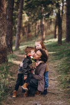 Молодая мать с дочерью и сыном в лесу