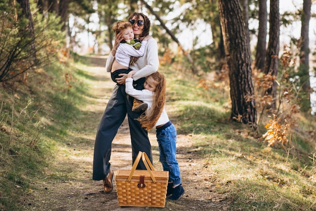 Giovane madre con la figlia e il figlio che camminano per il picnic nella foresta