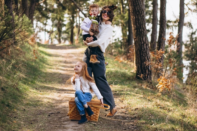 Young mother with daughter and son walking for picnic in the forest