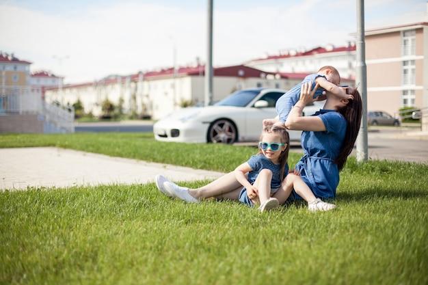 娘を持つ若い母親は草の上に座っています。