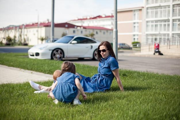 デニムのドレスに身を包んだ娘を持つ若い母親。家族の一見。幸せな家族