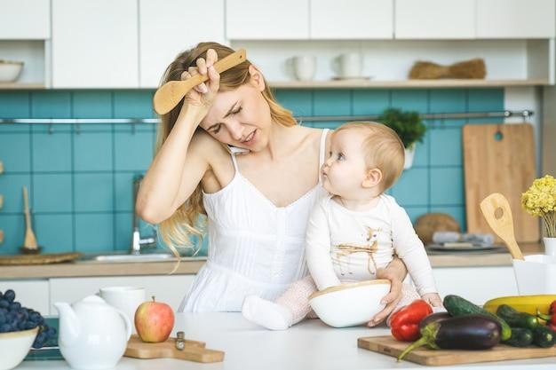 Молодая мать с дочерью ребенка в современной обстановке кухни. молодой привлекательный повар женщина отчаянно в стрессе, устал.