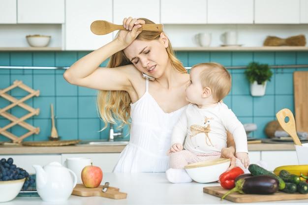 モダンなキッチンの設定で彼女の赤ん坊の娘を持つ若い母親。若い魅力的なクック女性は疲れて、ストレスで絶望的です。