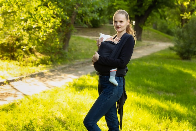 A young mother with her baby in a sling scarf is standing in a park.