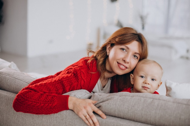 Young mother with her baby son sitting on sofa