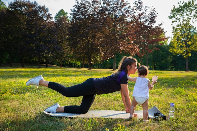 Young mother with her child do sports in park.