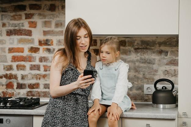부엌에서 그녀의 귀여운 딸과 함께 젊은 어머니