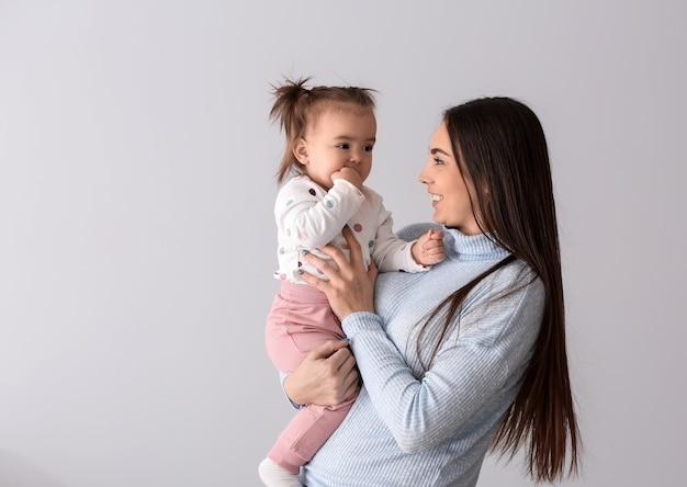 빛에 그녀의 귀여운 작은 딸과 함께 젊은 어머니