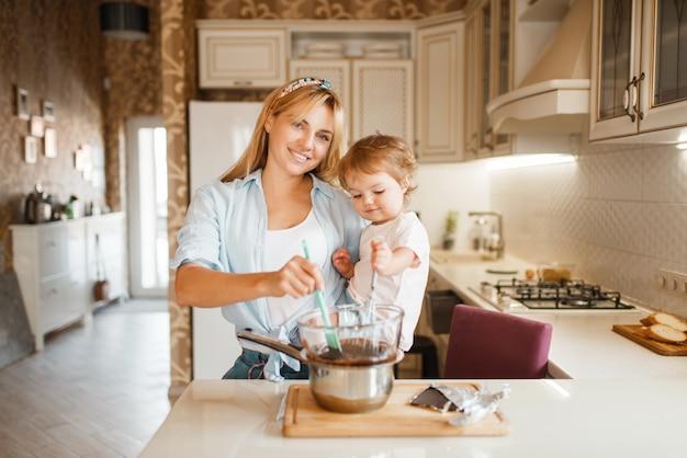 ボウルに溶かしたチョコレートを混ぜる彼女の娘を持つ若い母親。