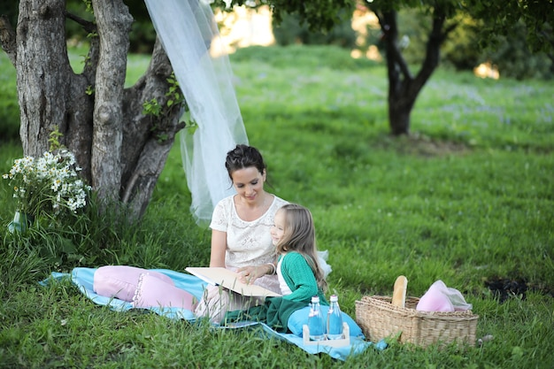 Young mother with her daughter at a picnic in the park