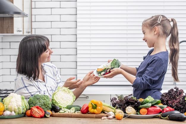 현대 가벼운 주방 인테리어의 배경에 많은 야채와 함께 그녀의 딸과 함께 젊은 어머니.