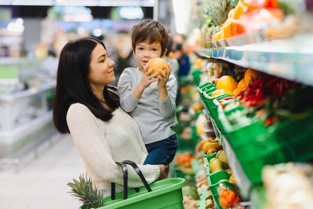 スーパーで彼女の小さな男の子を持つ若い母親