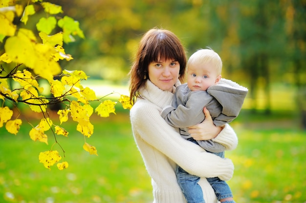Young mother with her little baby boy in the autumn park
