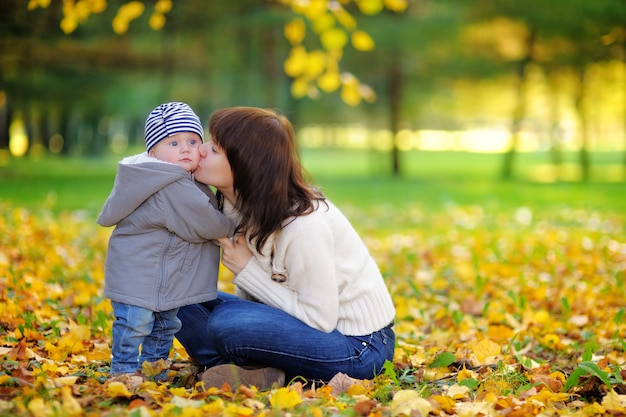 Young mother with her little baby boy having fun in the autumn park