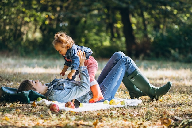 Young mother with her little daughter in an autumn park having picnic