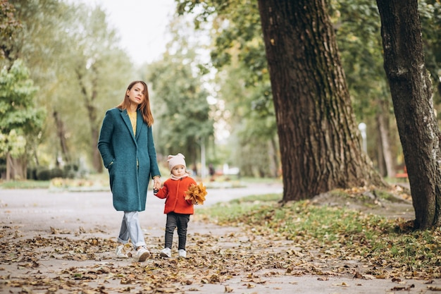 Young mother with her little daughter in an autumn park