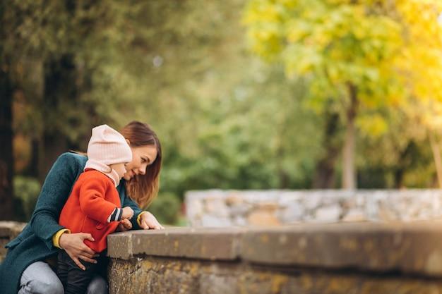 Giovane madre con la sua piccola figlia in un parco in autunno