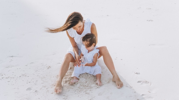 Young mother with her little daughter at the beach by the ocean