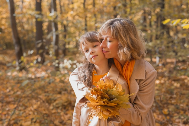 가을 공원 가을 시즌 육아와 어린이 개념에 어린 딸을 둔 젊은 어머니