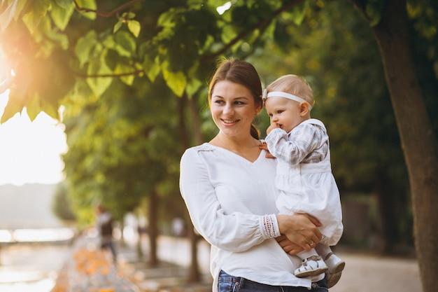 Молодая мать с маленькой дочкой в осеннем парке