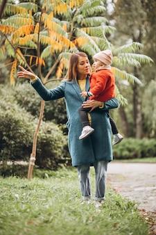 秋の公園で幼い娘と若い母親