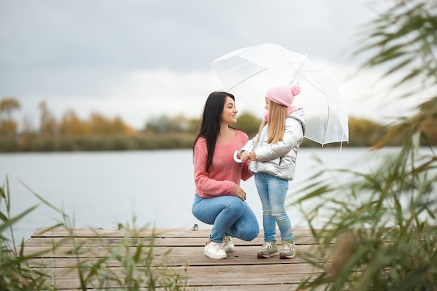 湖の近くの落下時間に彼女の小さな娘を持つ若い母親