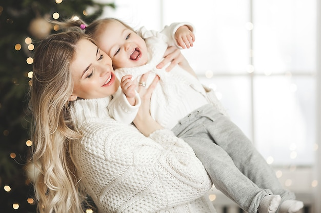 Молодая мать с маленькой дочерью на рождественском фоне