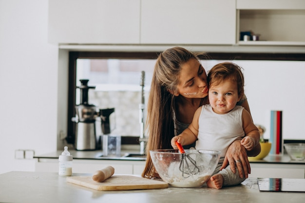 Young mother with her little son cooking at kitchen