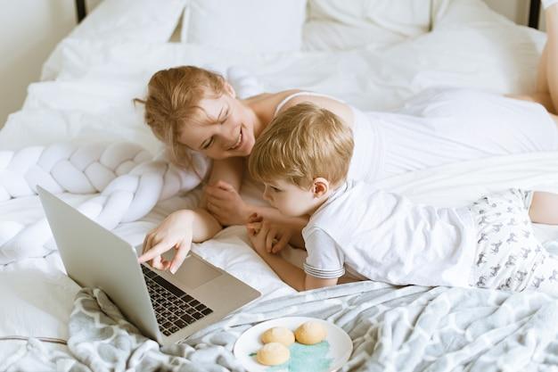 Молодая мать с маленьким сыном на кровати с ноутбуком