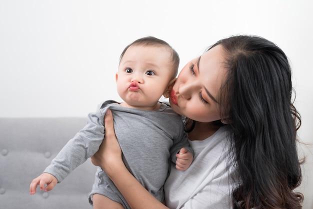 パジャマを着た1歳の幼い息子を連れた若い母親は、週末に一緒に居間で遊んだり、怠惰な朝を過ごしたり、暖かく居心地の良い場面でリラックスして遊んでいます.選択と集中。 Premium写真