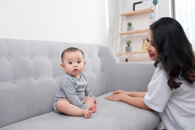 パジャマを着た1歳の幼い息子を連れた若い母親は、週末に一緒に居間で遊んだり、怠惰な朝を過ごしたり、暖かく居心地の良い場面でリラックスして遊んでいます.選択と集中。