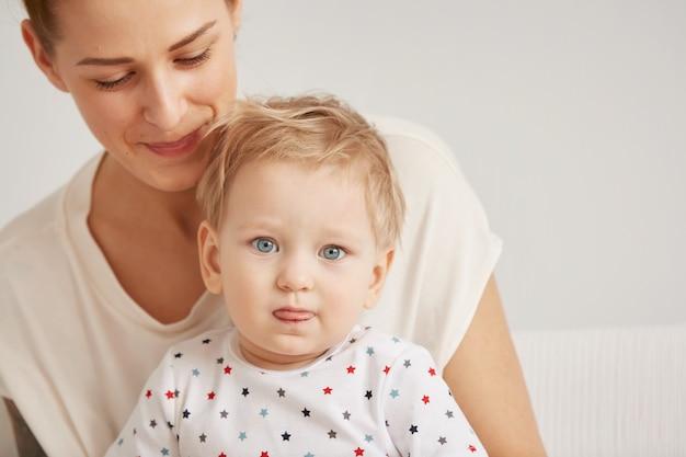 パジャマ姿の1歳の幼い息子を持つ若い母親がリラックス