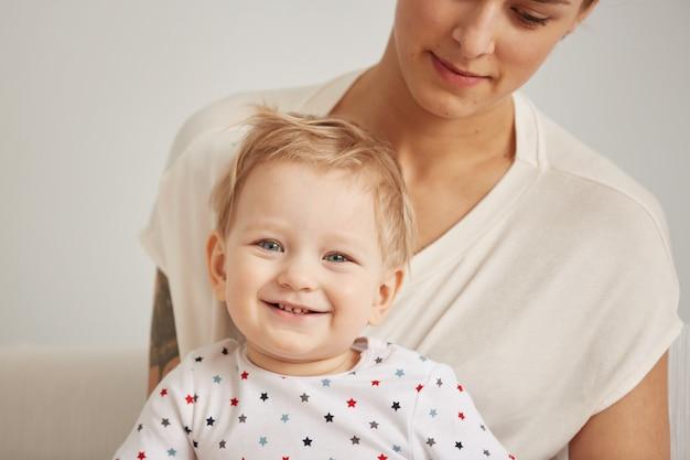 잠옷을 입은 그녀의 한 살짜리 작은 아들과 함께 젊은 어머니가 편안합니다.
