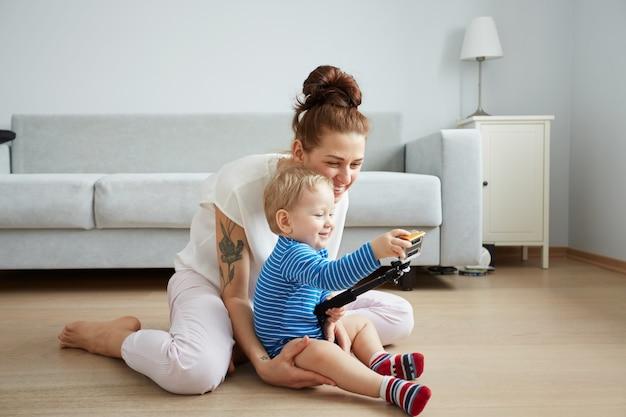 La giovane madre con il suo piccolo figlio di un anno vestito in pigiama sta proponendo