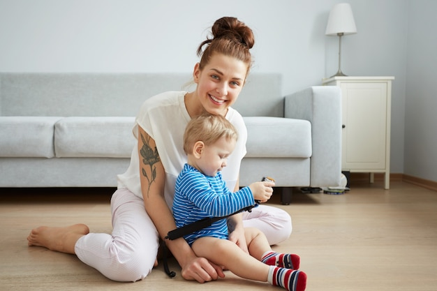 Young mother with her one years old little son dressed in pajamas are posing