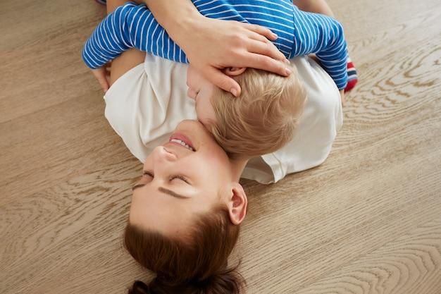 La giovane madre con il suo piccolo figlio di un anno vestito in pigiama si sta rilassando e abbracciando