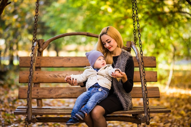 Young mother with her small son is resting on a wooden bench in the autumn golden park