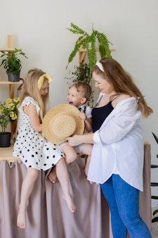 Young mother with her son and daughter laughs hugs and plays indoors concept of happy fun family