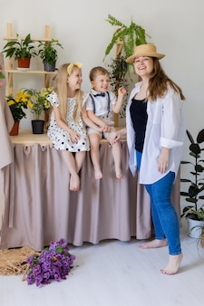 Young mother with her son and daughter laughs hugs and plays indoors with home flowers