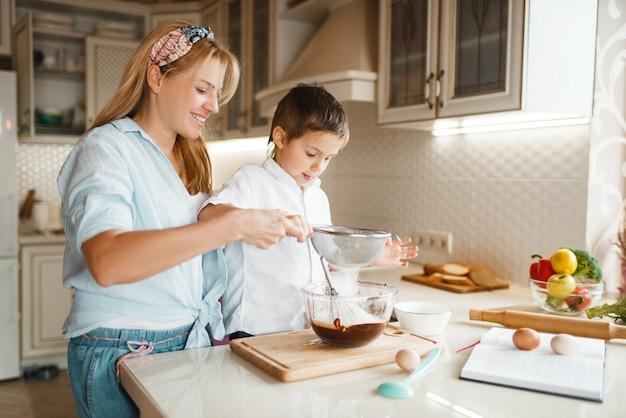 ボウルに溶かしたチョコレートを混ぜる息子と若い母親。