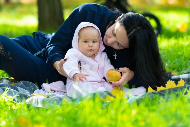 아이에게 신선한 가을 사과를 제공하는 무성한 녹색 잔디에 깔개에 앉아 공원에서 그녀의 작은 아기와 젊은 어머니