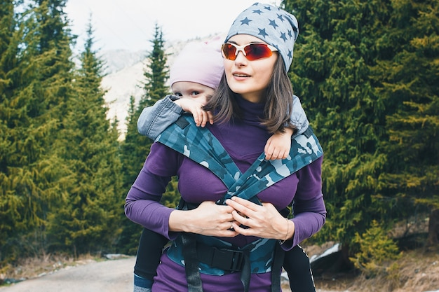 自然の中で人間工学に基づいたベビーキャリアで背中に彼女の幼児の娘を持つ若い母親家族のハイキング