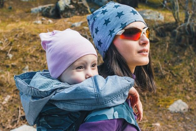自然の中で人間工学に基づいたベビーキャリアで背中に幼児の娘を持つ若い母親。